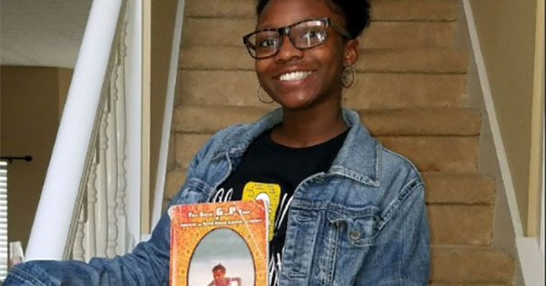 Jordyn Alexis Ash, the granddaughter of author Tyrone Ash, holds a copy of his book